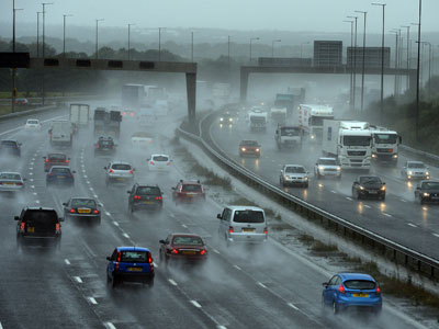 Cars drive through heavy rain at the Lymm interchange on the M6 in north-west England on September 25, 2012.(AFP Photo / Paul Ellis)