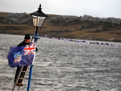 A man hangs a Falklands flag in Stanley.(Reuters / Enrique Marcarian)
