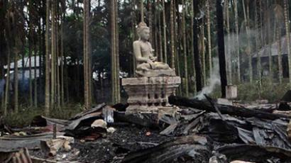 A statue of Lord Buddha is left standing amidst the torched ruins of the Lal Ching Buddhist temple at Ramu, some 350 kilometres (216 miles) from the capital Dhaka on September 30, 2012 (AFP Photo)