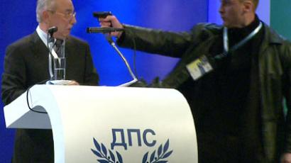 WARNING: GRAPHIC CONTENT. This video grab broadcast by Bulgarian television channel BTV shows a man (R) pointing a pistol at leader of the Turkish minority Movement for Rights and Freedoms (MRF) party Ahmed Dogan during his speech at a national party conference in Sofia on January 19, 2013.(AFP Photo /BTV)