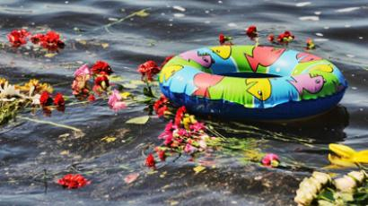 Flowers and a children's rubber ring seen on water during memorial events held at Kazan's river port to mourn the Bulgaria cruise boat victims. (RIA Novosti/Grigory Sysoev)