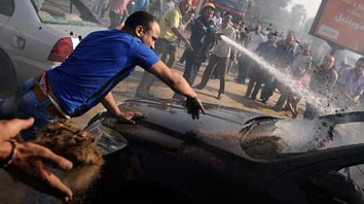 Egyptian firefighters and bystanders try to extinguish several cars that caught on fire outside the Nile City Towers during clashes between Egyptian policemen and an unknown mob from a near by neighbourhood in Cairo on August 2, 2012 (AFP Photo / Mohamed Hossam)