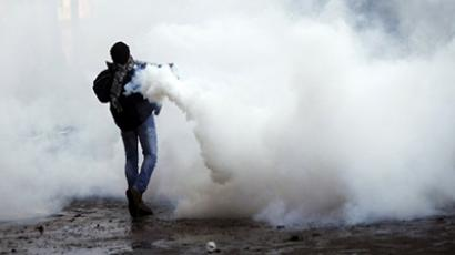 A protester throws back a tear gas canister during clashes with Egyptian riot Police on Tahrir Square on November 28, 2012 in Cairo. (AFP Photo / Mahmoud Khaled)