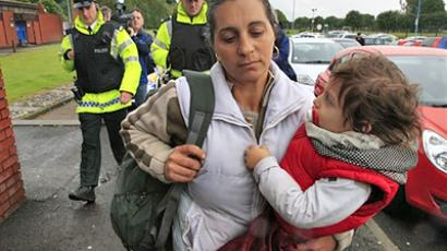 United Kindom, Belfast : A Romanian woman and her child are escorted by police into the Ozone Leisure Centre in Belfast, in Northern Ireland, on June 17, 2009. (AFP Photo / Peter Muhly)
