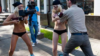 An embassy employee attacked first the topless activists, and then one of the journalists
