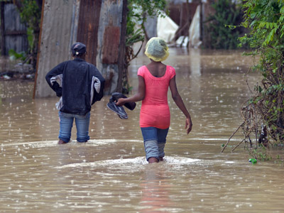 Haitians walk through a street flooded by rains from Hurricane Sandy in Port-au-Prince October 26, 2012. (Reuters/Swoan Parker)