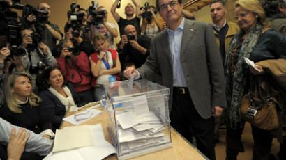Current President of Catalonia and leader of the CiU (Catalan Convergence and Unity) party Artur Mas (2ndR) looks on as he casts his ballot for regional elections in Barcelona on November 25, 2012 (AFP Photo / Lluis Gene)