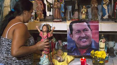 Nancy Romero places a figurine on a religious altar with images of Venezuela's President Hugo Chavez in Caracas January 3, 2013. (Reuters / Carlos Garcia Rawlings)