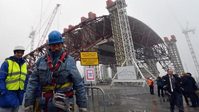 Workers are picture after the raising of the first section of a colossal arch-shaped structure that is eventually to cover the exploded reactor at the Chernobyl nuclear power station, on November 27, 2012 in Chernobyl. (AFP Photo / Sergei Supinsky)