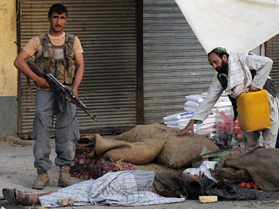 An Afghanistan's policeman stands guard near the body of a Taliban fighter in Kandahar city on July 9, 2012. (AFP Photo/Jangir)