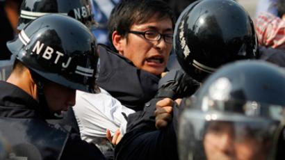 Police officers arrest a protester during a protest against plans to expand a petrochemical plant in Ningbo, Zhejiang province October 27, 2012 (Reuters / Carlos Barria)