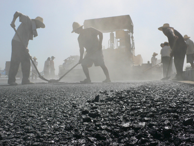 Workers pave a new road under construction in Kaifeng, Henan province (Reuters / China Daily)