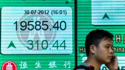 A man walks before a share prices board in Hong Kong on July 30, 2012. Asian markets mostly rose for a second straight session July 30 on hopes for new rounds of central bank stimulus in the United States. (AFP Photo / Philippe Lopez)