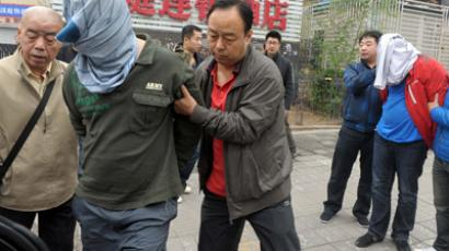 This picture taken on April 20, 2012 shows Chinese police detectives detaining a man in Beijing, after they searched his home for evidence on using the internet to commit various criminal activities using personal information of citizens stolen off websites. (AFP Photo)
