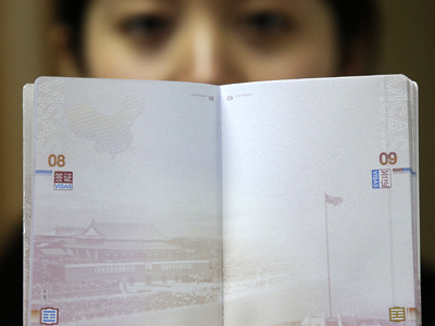 A woman holds a Chinese passport, displaying a Chinese map which includes an area in the South China Sea inside a line of dashes representing maritime territory claimed by China (L, top) and a picture of Beijing's Tiananmen Square (bottom), November 23, 2012. (Reuters / Darley Shen)
