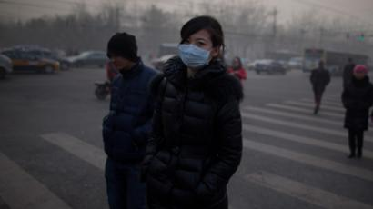 A woman wearing a mask crosses a road during severe pollution in Beijing on January 12, 2013 (AFP Photo / Ed Jones)