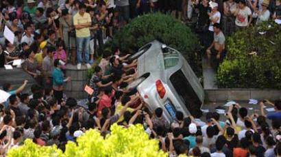 CHINA, Qidong : A group of protesters overturn a car near the local government office compound in the coastal city of Qidong, near Shanghai, in the eastern China province of Jiangsu on July 28, 2012. (AFP photo / Peter Parks)