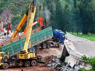 The driver, named by Chinese media only as Mr. Zhang, was driving a truck filled with sand which was so overloaded that the concrete bridge collapsed when he took his lorry across it (AFP Photo / Getty Images)