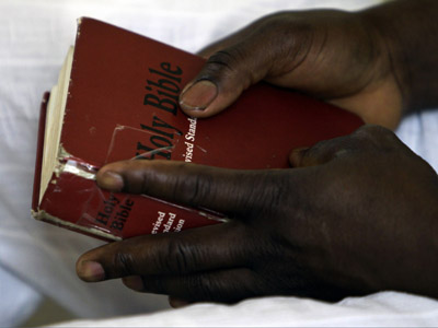 A Christian Catholic man living in Libya holds a Bible (AFP Photo/Joseph Eid)