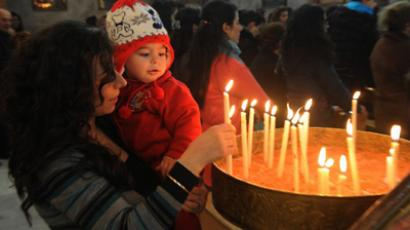 A Syrian  woman lights a candle during early Christmas eve mass, at the Mar Elias (St. Elijah) Christian Orthodox church in Bab Tuma, a predominantly Christian quarter of Damascus, on December 24, 2012. (AFP Photo)