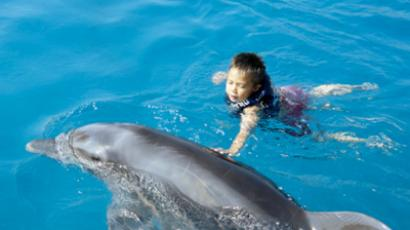 A Moscow dolphinarium offers therapy to children suffering from physical and mental disabilities