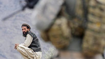An Afghan villager looks on as a US soldier from the Provincial Reconstruction team (PRT) Steel Warriors patrols in the mountains of Nuristan Province (AFP Photo / Tauseef Mustafa)