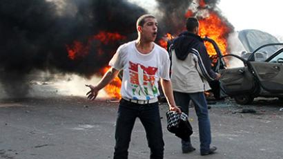An anti-Morsi protester shouts slogans in front of burning cars during clashes with Morsi supporters in Alexandria December 14, 2012. (Reuters/Stringer)