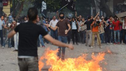 Opponents of the Muslim Brotherhood and President Mohamed Morsi throw Molotov cocktails towards government supporters during clashes in Tahrir square in Cairo on October 12, 2012 (AFP Photo / Khaled Desouki)