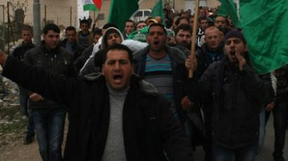 Palestinian mourners shout slogans and wave green Islamic flags as they carry the body of Mohamed Ziad Salayma during his funeral procession on December 13, 2012, after he was killed the previous day by Israeli forces near his home in the old city of the West Bank town of Hebron. (AFP Photo/Hazem Bader)