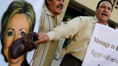 An Egyptian protester shouts slogans as he holds a shoe on a portrait of US Secretary of State Hillary Clinton outside the US embassy in Cairo on July 14, 2012 to protest against her visit to the country (AFP Photo / Mohhamed Hassam)