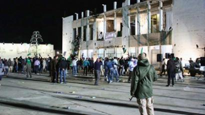 Libya, Tripoli: People mill around near Libyan leader Moamer Kadhafi's residence after a missile totally destroyed an administrative building in the Libyan leader's complex in Tripoli on March 20, 2011. (AFP Photo / Imed Lamloum)