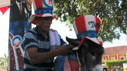 A friend of Colombian attorney Silvio Carrasquilla dresses a baby donkey Demo as the mascot of the U.S. Democratic Party in front of a poster of U.S. President Barack Obama, outside Carrasquilla's home in Turbaco, near Cartagena April 11, 2012 (Reuters/Joaquin Sarmiento)