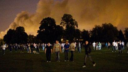 A large group of people walk across a field towards a housing estate as they patrol Enfield, north London, in an effort to protect the community against looters early on 10 August 2011 (AFP Photo / Andrew Cowie)