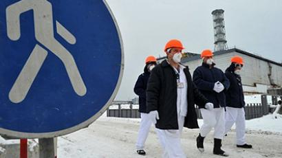 Ukraine, Chernobyl: Employees of the Chernobyl Nuclear Power Plant walk in front of the destroyed 4th block of the plant on February 24, 2011 ahead of the 25th anniversary of the meltdown of reactor number four due to be marked on April 26, 2011. (AFP Photo / Sergey Supinsky)