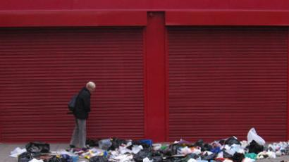 A woman looks through what remains of donations that had been left outside a charity shop overnight in east London.(Reuters / Russell Boyce)