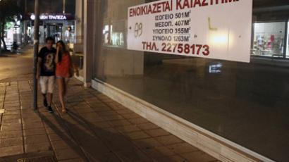 "A Cypriot couple walk past a closed shop with a sign reading in Greek: ""For rent"" in the east Mediterranean island's capital Nicosia on June 20, 2012 (AFP Photo/Yiannis Kourtoglou)"