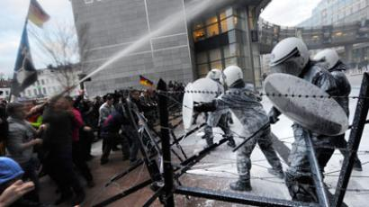 Dairy farmers spray milk to riot police during a protest against EU agricultural policies at the Place du Luxembourg, near the European Parliament, in Brussels, on November 26, 2012.(AFP Photo / John Thys)