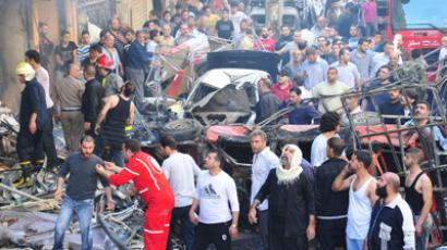 A crowd gathers in front of a building damaged after a car bomb in Jaramana district, near Damascus, in this handout photograph released by Syria's national news agency SANA October 29, 2012 (Reuters / Sana)