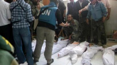 Houla: A handout picture released by the Syrian opposition's Shaam News Network shows UN observers inspecting the bodies of 92 victims at a hospital morgue before their burial in the central Syrian town of Houla on May 26, 2012 (AFP Photo / Shaam News network)