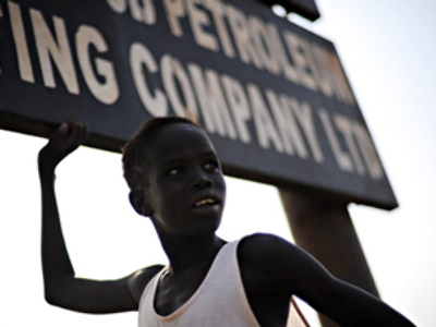 Sudan, New Rier: Thirteen year-old Peter stands on November 11, 2009 underneath a sign announcing the petroleum company which relocated the village that he and some other 2500 villagers in the south central town of Rier used to habitate. (AFP Photo / Roberto Schmidt)