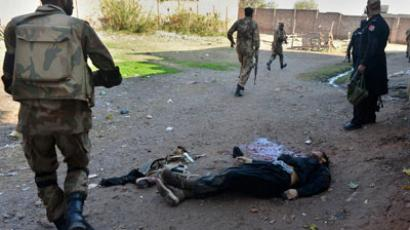 Pakistani army soldiers run past the dead body of Taliban militant during a gun battle with militants in Peshawar on December 16, 2012.(AFP Photo / A Majeed)