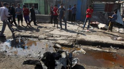 Iraqis inspect the site of a bomb attack at Al-Bawia market, in the east Baghdad district of Maamal, on October 27, 2012, where at least five people were killed and 13 others were wounded (AFP Photo / STR)