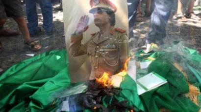 Demonstrators set fire to a poster of Libyan leader Muammar Gaddafi, copies of his Green Book and Libyan flags (AFP Photo / Adem Altan)