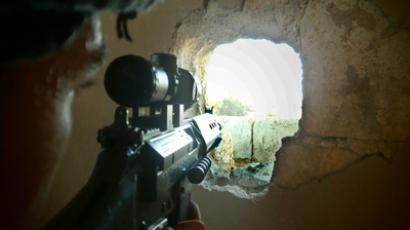 A member of the Free Syrian Army points his weapon through a hole in a wall as he takes up a defense position in a house in Qusseer neighbourhood in Homs July 16, 2012 (Reuters/Shaam News Network/Handout)