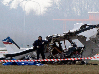 A police photographer inspects the scene of a tourist plane crash at Charleroi airport February 9, 2013 (Reuters / Sebastien Pirlet)