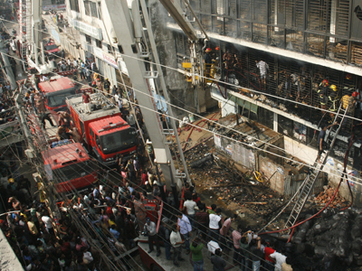 Bangladeshi firefighters stand in a burned out bulding as they try and control a fire that broke out at a garment factory on the outskirts of Dhaka on November 26, 2012 (AFP Photo / Str)