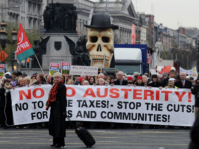 A woman pulling a suitcase crosses the road as protestors march against Government austerity measures in Dublin, Ireland on November 24, 2012. (AFP Photo / Barry Cronin)