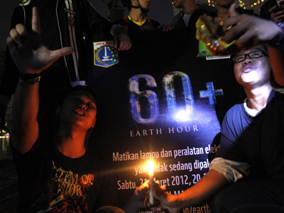 Youths hold candles as they participate in Earth Hour after lights were turned off at the Welcome Statue in Jakarta March 31, 2012. (Reuters / Supri Supri)