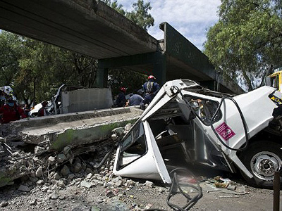 Mexico City : Firefighters work to remove a bus damaged by a bridge which collapsed, following a strong quake that hit Mexico on March 20, 2012 (AFP Photo/Ronaldo Schemidt)