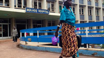 A woman walks on July 31, 2012 near the entrance to the Mulago Hospital in Kampala, where one person who contracted the deadly Ebola virus died. (AFP Photo / Michele Sibilone)